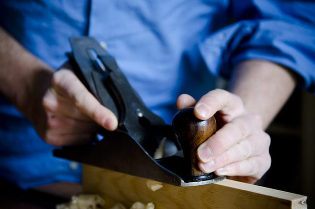 Stanley #4 smoothing hand planer or hand plane being used on a board's edge