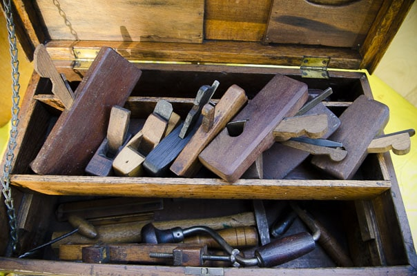 Antique Tool Chest Filled With Woodworking Hand Tools Like Hand Planes, Braces, And Hammers