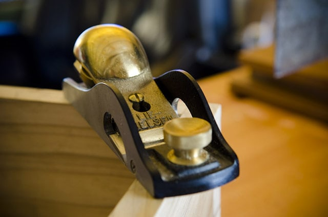 Lie-Nielsen brass low angle rabbet block plane sitting on a dovetail box