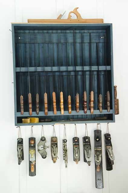 Blue Hand Saw Till and Hand Planer Tool Cabinet with hand planes hanging from the bottom