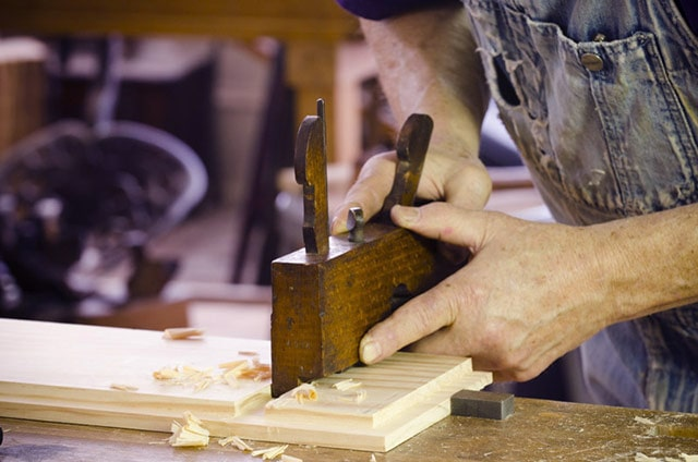 Woodworker cutting dado joint with an Antique Wood Dado Plane or hand planer