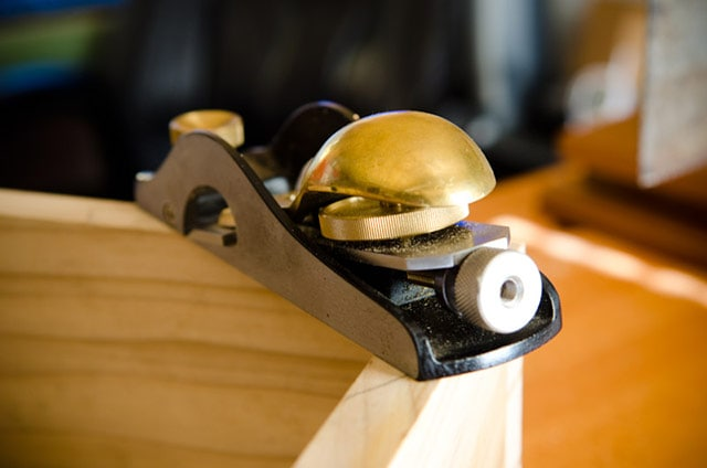 Rear of a Lie-Nielsen brass low angle rabbet block plane sitting on a dovetail box