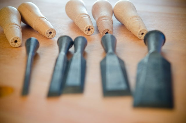 Wood chisel socket handles in focus on a woodworking workbench with antique socket chisels blurred in the foreground