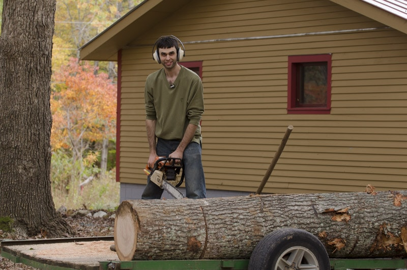 Elia Bizzarri using a chainsaw to cut a log for windsor chair making