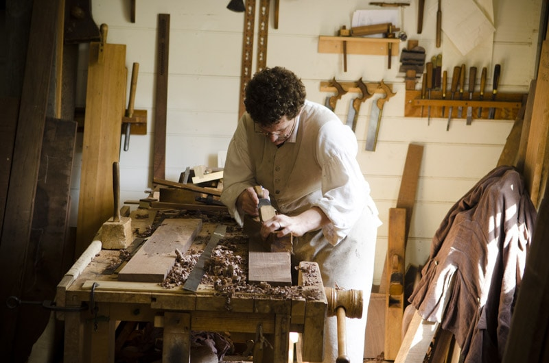 Brian Weldy hand planing a walnut board in the Hay Cabient making shop in Colonial Williamsburg
