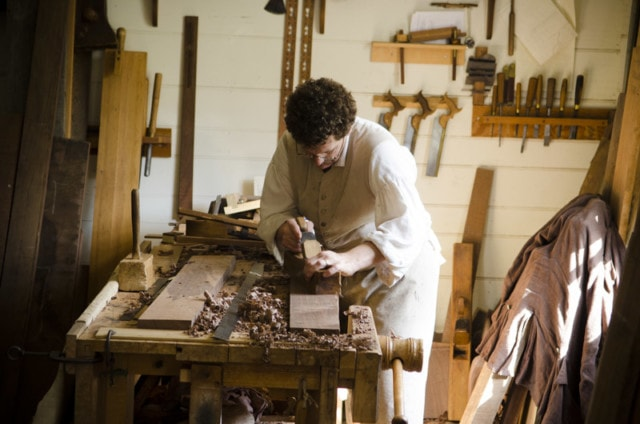 Brian Weldy Colonial Williamsburg hay cabinet shop hand planing a board on a workbench