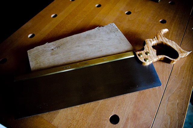 Lie-Nielsen tenon brass back saw with figured maple handles on a woodworking workbench