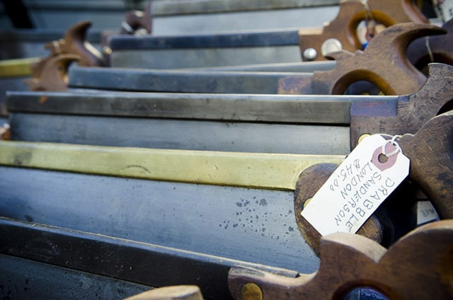 Row of antique back saw hand saws at a tool sale. Tag says Drabble Sanderson London. $45.00.