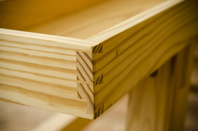 Through dovetails that hide a plowed groove on a pine workbench tray