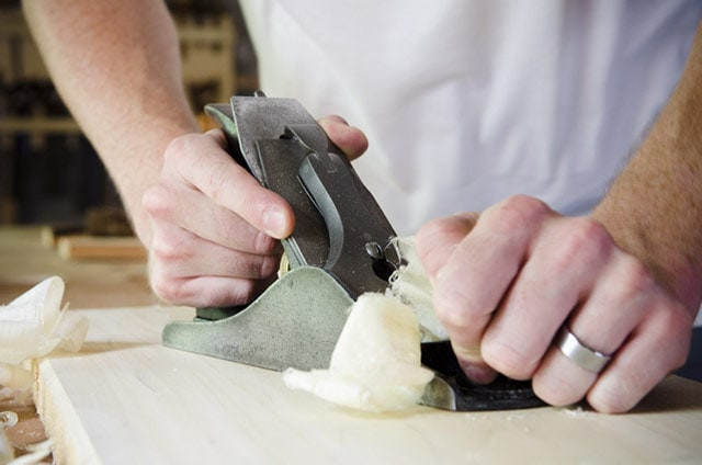 Man using a Stanley No. 4 smoothing plane to smooth a poplar board