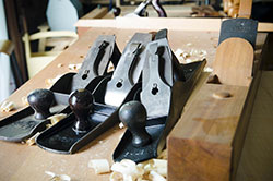 Stanley planes sitting on a woodworking workbench next to a wood plane