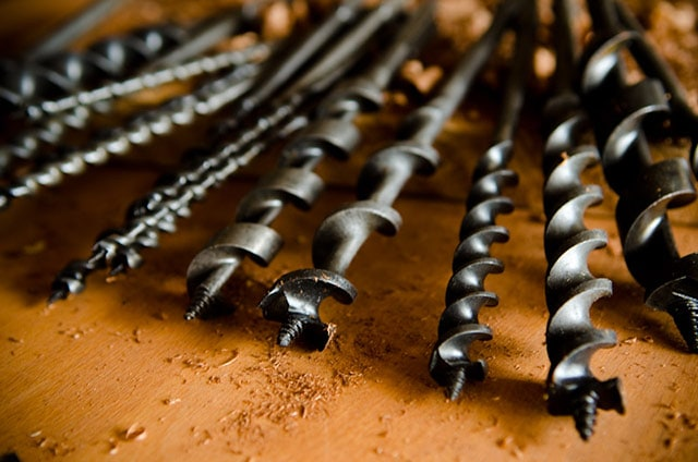 Irwin And Jennings Antique Auger Bits For A Brace And Bit Manual Hand Drill Sitting On A Wood Work Bench