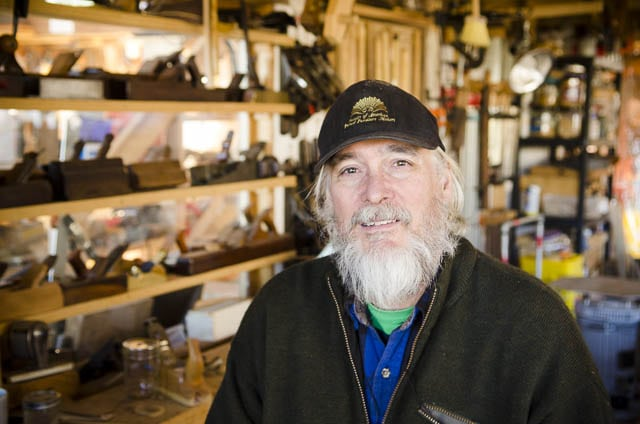 Don Williams portrait in his workshop sitting in front of a display of hand planes or hand planers