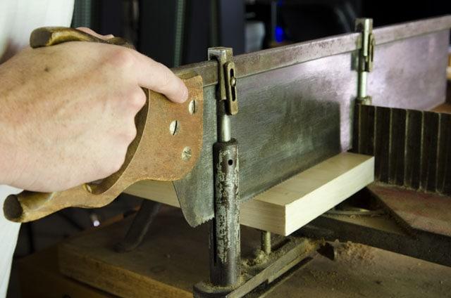 Miter box saw cross cutting a board