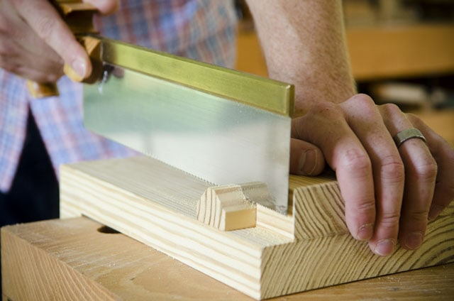 Cutting a piece of southern yellow pine on a bench hook with a Lie-Nielsen cross cut carcass saw on a woodworking workbench