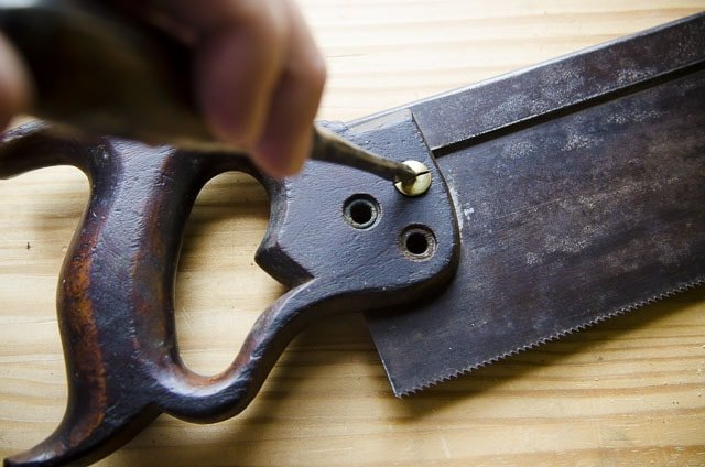 Unscrewing a brass hand saw nut from an antique Simonds 97 back saw on a woodworking workbench