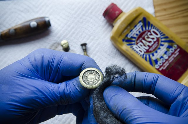 Polishing a brass antique Simonds 97 hand saw medallion with bottle of Brasso brass polish on the woodworking workbench