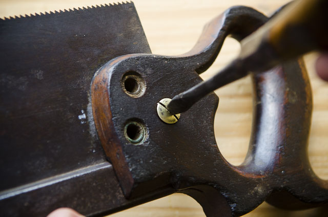 Screwing a brass hand saw nut onto an antique Simonds 97 back saw on a woodworking workbench