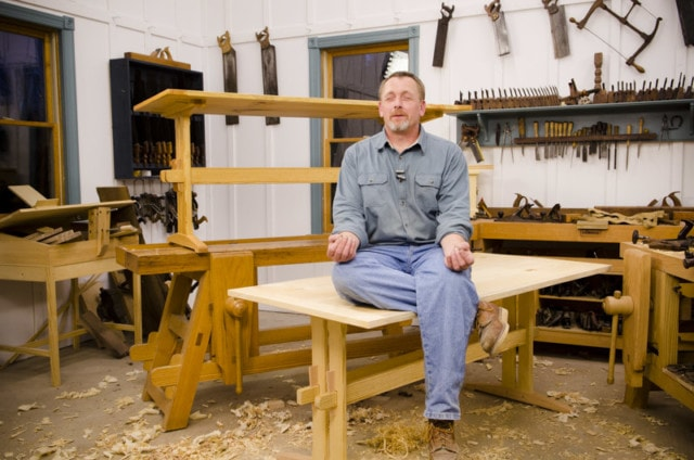 Will Myers Sitting On The Finished Trestle Table In A Funny Zen Position Next To Woodworking Workbenches In Joshua Farnsworth'S Woodworking Workshop