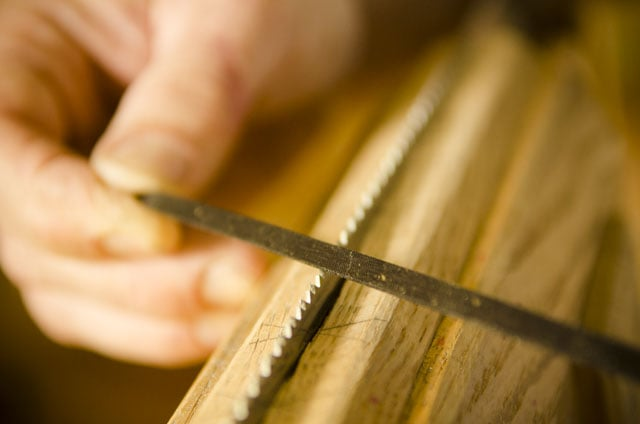 Close-up view of Tom Calisto filing and sharpening hand saw teeth with a triangular saw file