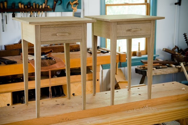 Two ammonia fumed quartersawn white oak night stands in a woodworking workshop