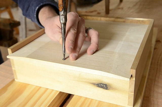 Attaching a drawer bottom into a drawer frame on a nightstand table with a screw and screwdriver