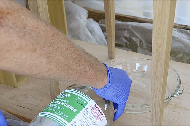 Pouring ammonium hydroxide ammonia in a glass pan for ammonia fuming white oak end tables and drawers