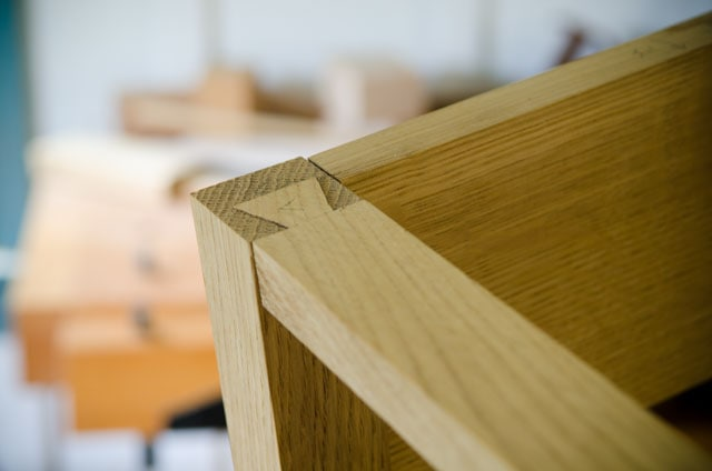 Lapped dovetail joint drawer rail inserted into a table leg