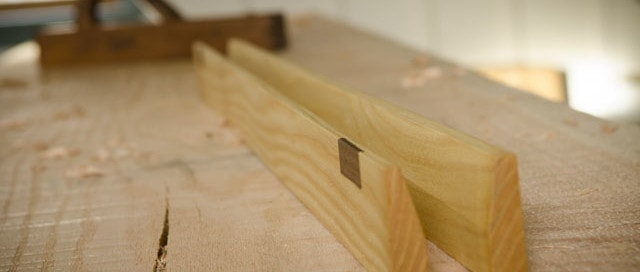 Wooden winding sticks sitting on red oak roubo workbench slab with hand planer in background