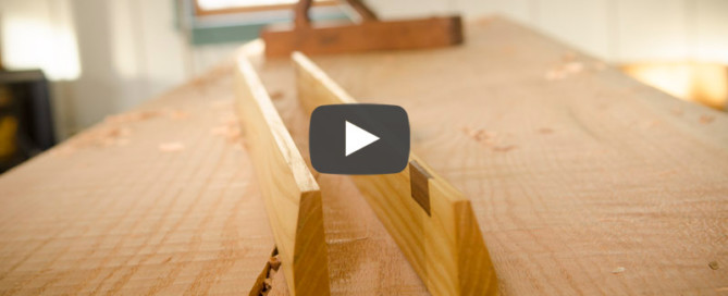 Wooden winding sticks on a woodworking workbench with hand planer in background in joshua farnsworth's workshop video player icon