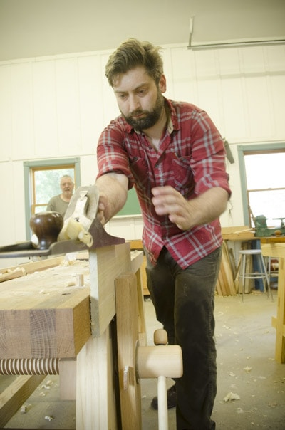 An bearded woodworking student using an antique Stanley 7 jointer plane at a woodworking workbench