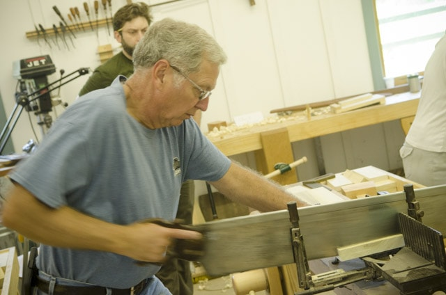 A male woodworking student cutting a board with an antique miter box saw