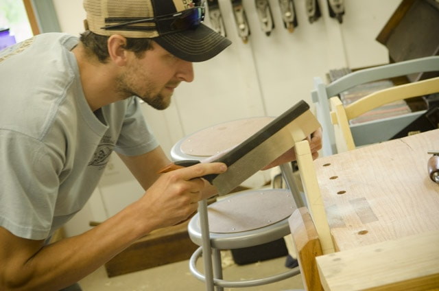 A young male woodworking student using a dovetail saw to cut dovetail joints