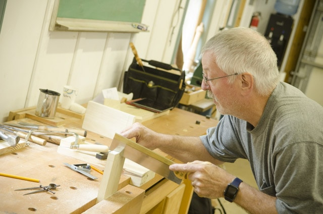 An older woodworking student using a dovetail saw to cut dovetail joints