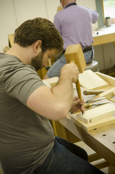 Bearded woodworking student using a chisel and joiner's mallet to make a dovetail joint