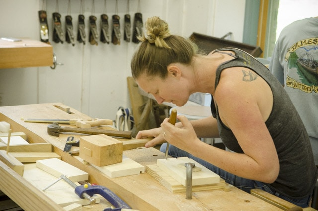 A female woodworking student using a chisel and joiner's mallet to make a dovetail joint