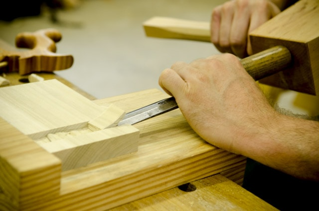 closeup of a woodworking student using a chisel and joiner's mallet to cut a dado joint
