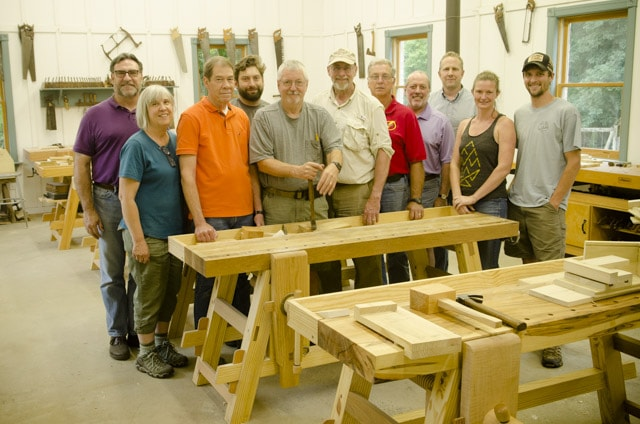 Class of woodworking students standing around Moravian workbenches