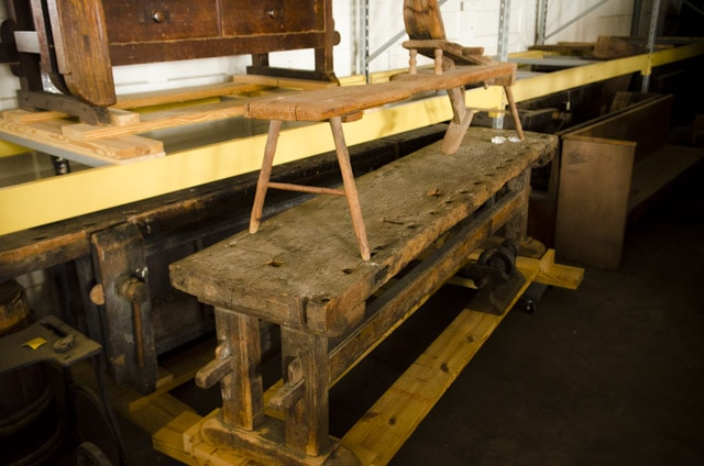 An antique shaving horse sitting on top of an antique moravian workbench at old salem