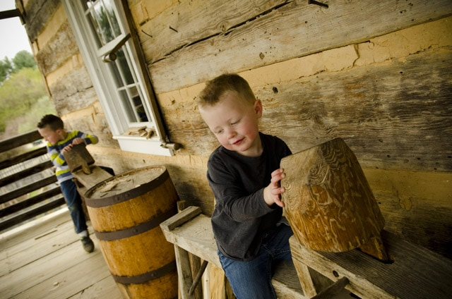 Little boy sitting on a woodworking shaving horse at the Frontier Culture Museum