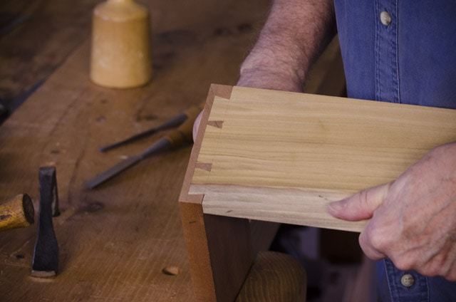 James Hugget making a half blind dovetails joint for drawers out of Mahogany drawer front and poplar wood sides, with chisels and a mallet on a woodworking workbench