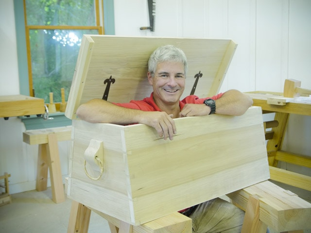 Tom Calisto popping his head and arms out of an angled dovetail sailor tool chest in Joshua Farnsworth's Traditional Woodworking School