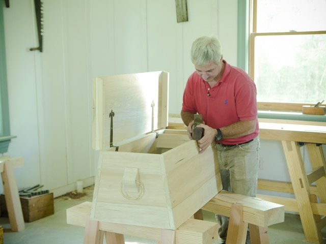 Tom Calisto using an antique hand plane to make an angled dovetail sailor tool chest in Joshua Farnsworth's Traditional Woodworking School
