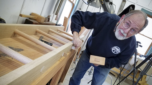 older man using a mallet to drive wedges on an oak ladder