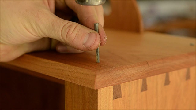 A hand holding a cut nail to attach a top with a hammer on a shaker wall cupboard