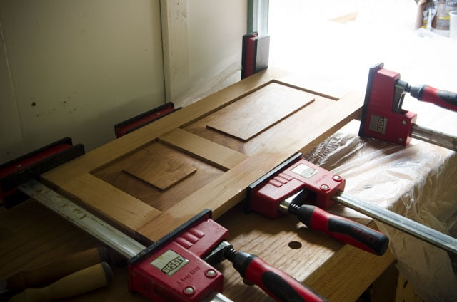 Frame and Panel door being glued up with woodworking clamps for a cherry shaker wall cupboard