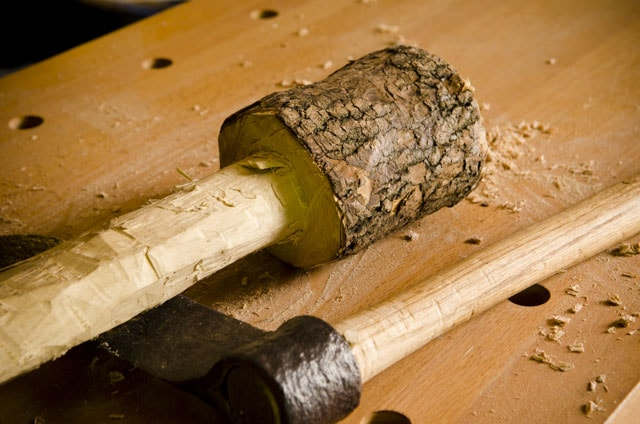 Green woodworking wooden maul mallet with froe on a woodworking workbench