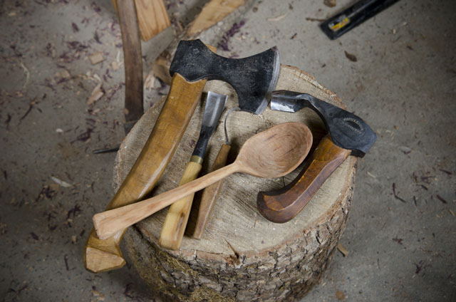 Green woodworking tools on a stump, including carving hatchet, carving gouge, hook knife, bowl adze, and wooden spoon