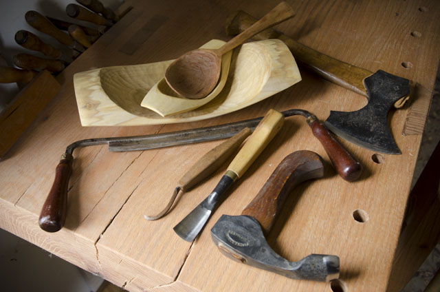 Green woodworking tools on a woodworking workbench, including carving hatchet, carving gouge, hook knife, bowl adze, draw knife, and wooden spoon inside a wooden bowl