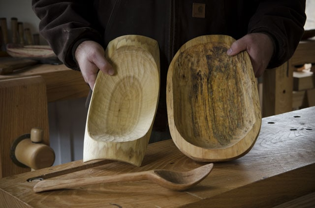 Mike Cundall demonstrating two wooden bowls and spoons that he made